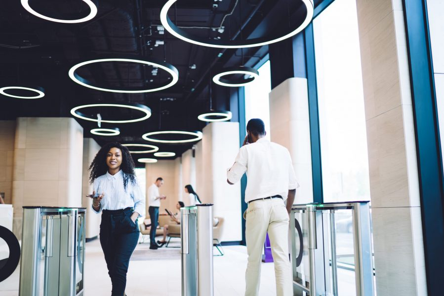 Low angle of glad African American staff in stylish clothes passing through turnstile while using smartphone in hall of contemporary business center